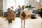 Excited kids playing holding boxes after moving in new home