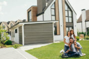 Family sitting on lawn in backyard, big modern house on background